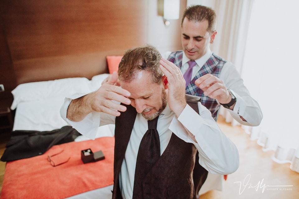 El novio colocándose el pelo antes de ponerse la chaqueta