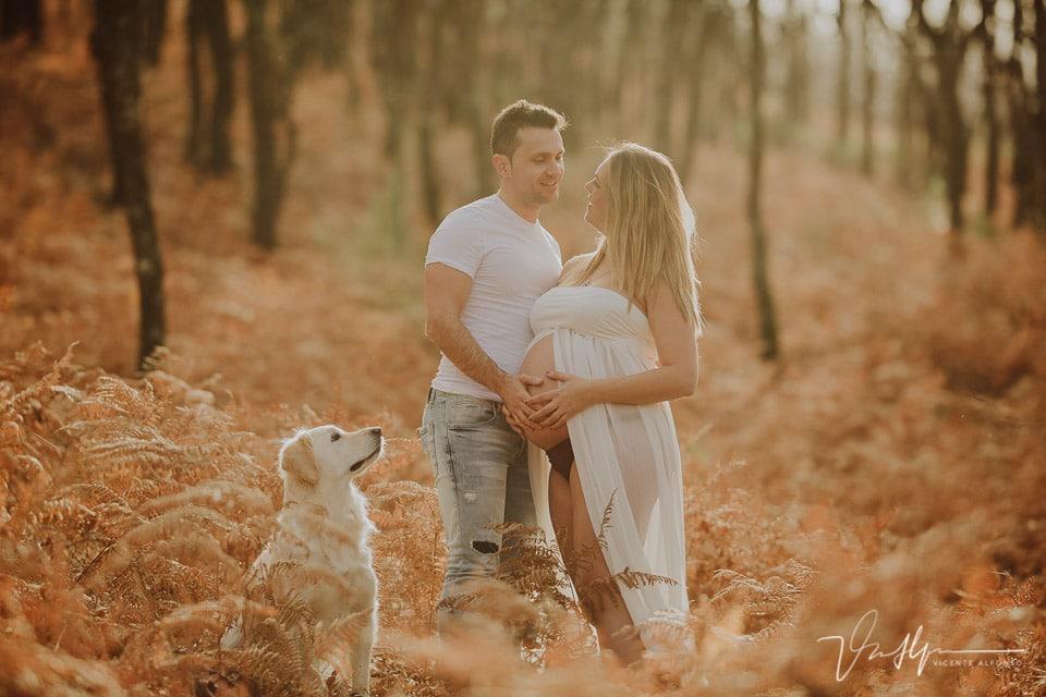 Pareja embarazada mirándose junto a su perro en la Sierra