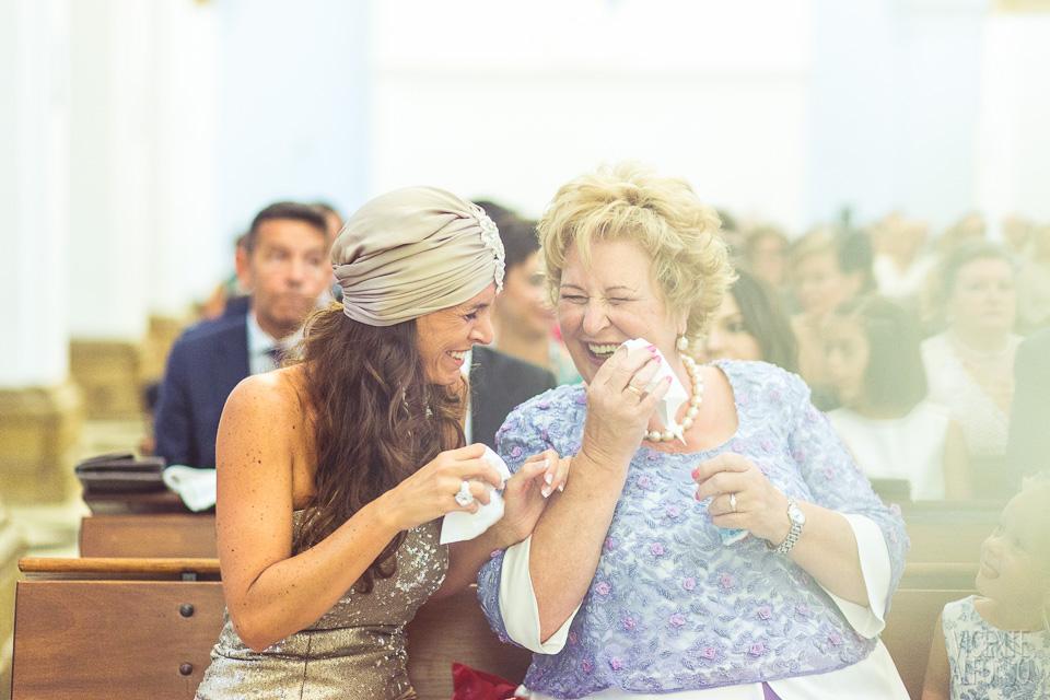 La madre y la hermana de la novia llorando de risa en la iglesia