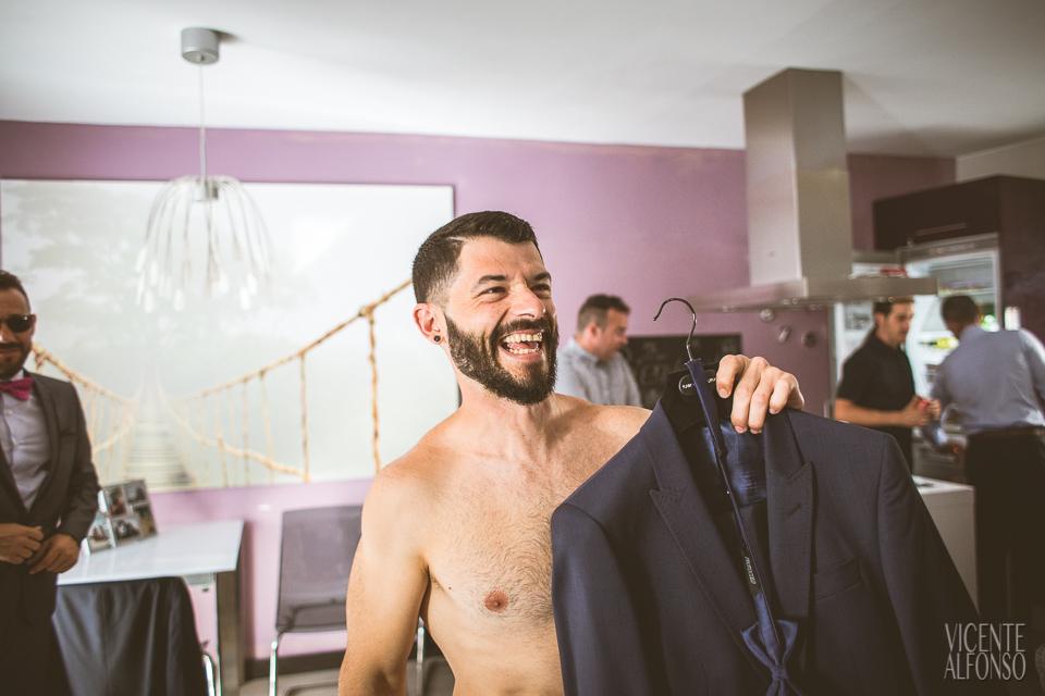 Novio sin camisa sujetando chaqueta