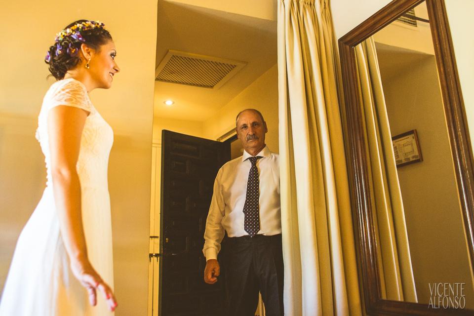 Novia terminándose de vestir y su padre mirando