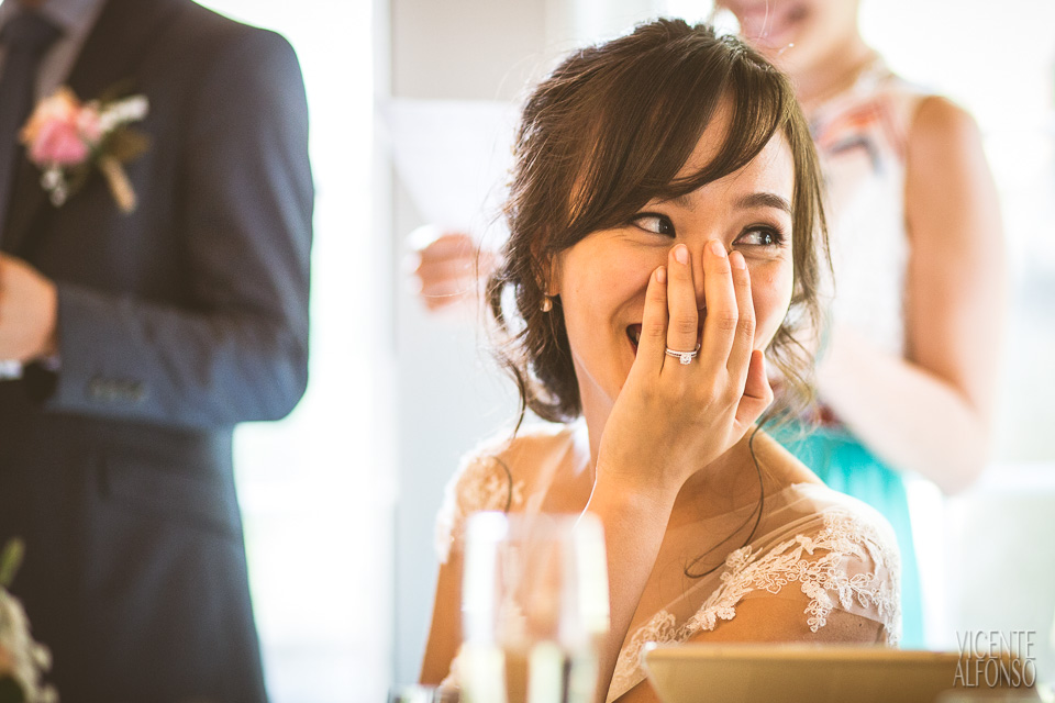 Novia vietnamita riendo con mano en la boca