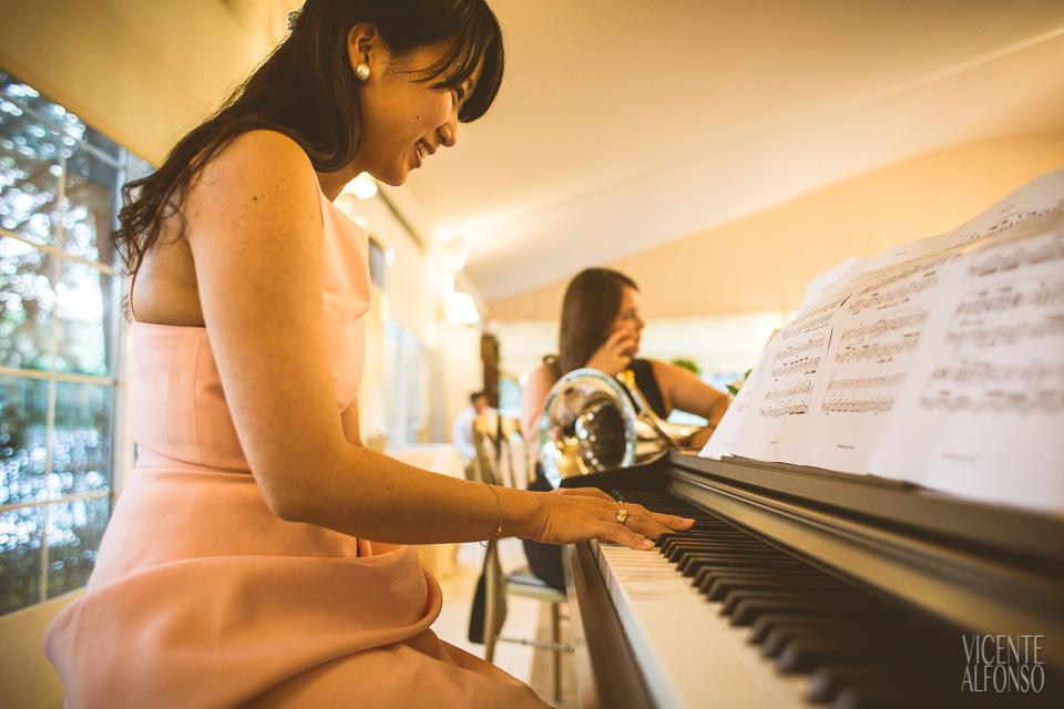Amiga vietnamita de la novia tocando el piano en el baile