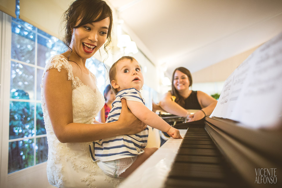 Novia con bebé tocando piano en su boda