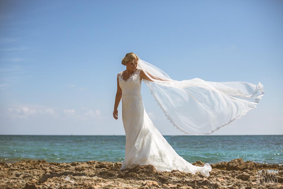 Retrato novia con el velo volando sobre la playa