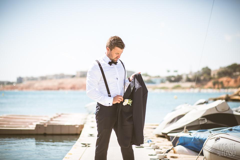Novio cogiendo su chaqueta en el puerto
