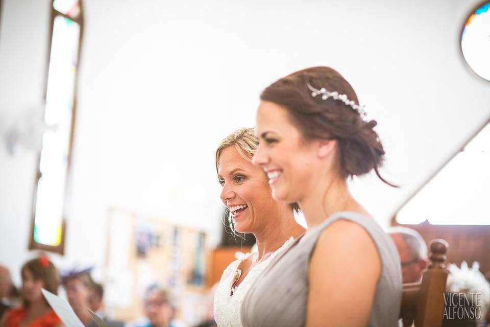 Novia y madrina riendo en la iglesia