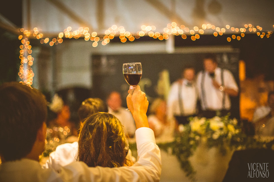 Brindando con vaso de vino y bokeh de luces