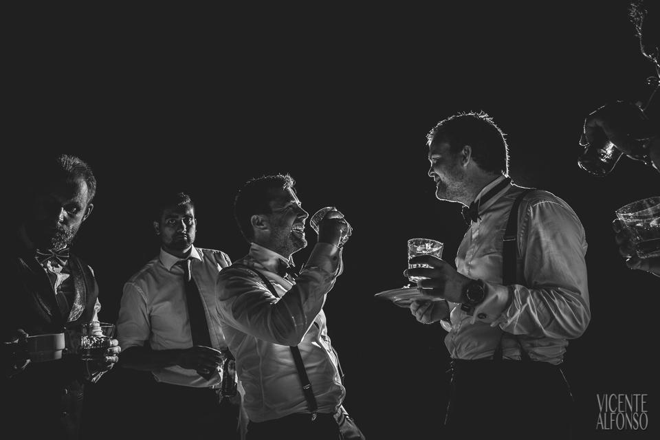 El novio y los amigos bebiendo Whiskey y charlando
