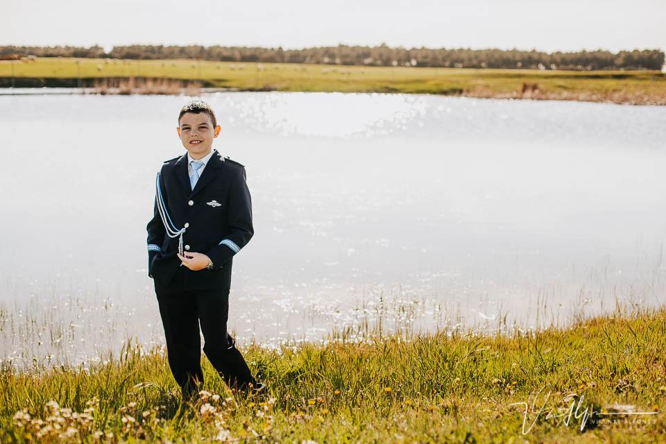 Niño de comunión junto a una laguna