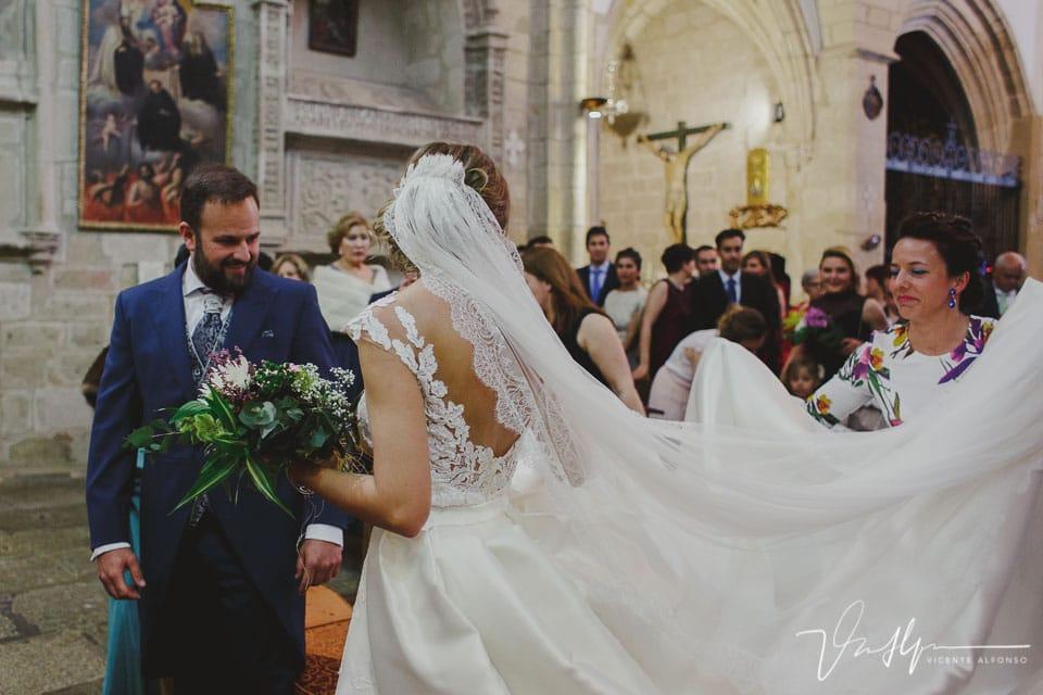 Amiga sujetando el velo de la novia dentro de la iglesia