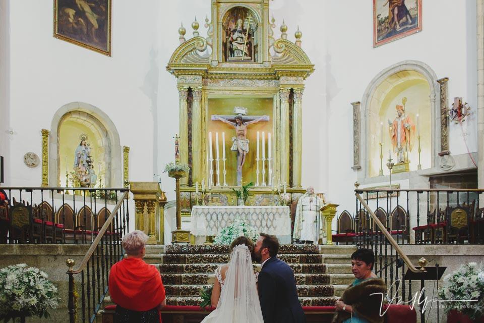 Novio besando a la novia en el altar de la Iglesia de San Martín