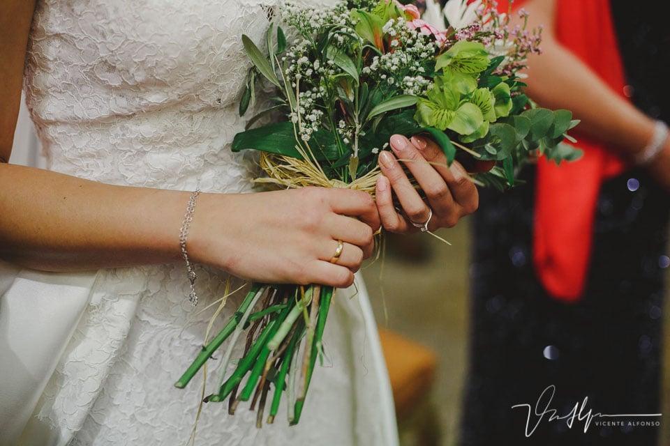 Detalle de las manos y ramo de flores de la novia