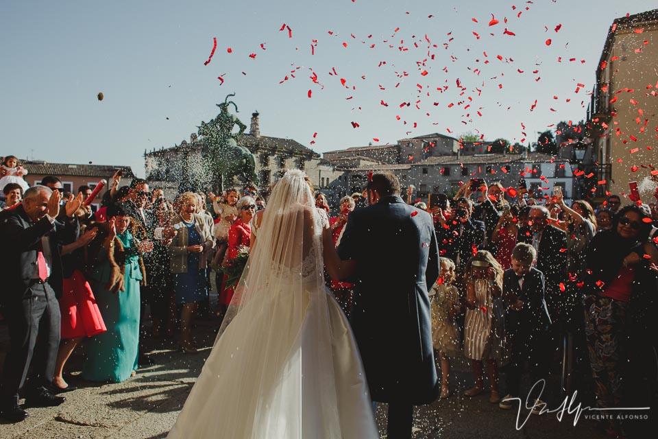 Detalle salida de la iglesia con los novios de espaldas a cámara y con confeti y pétalos volando