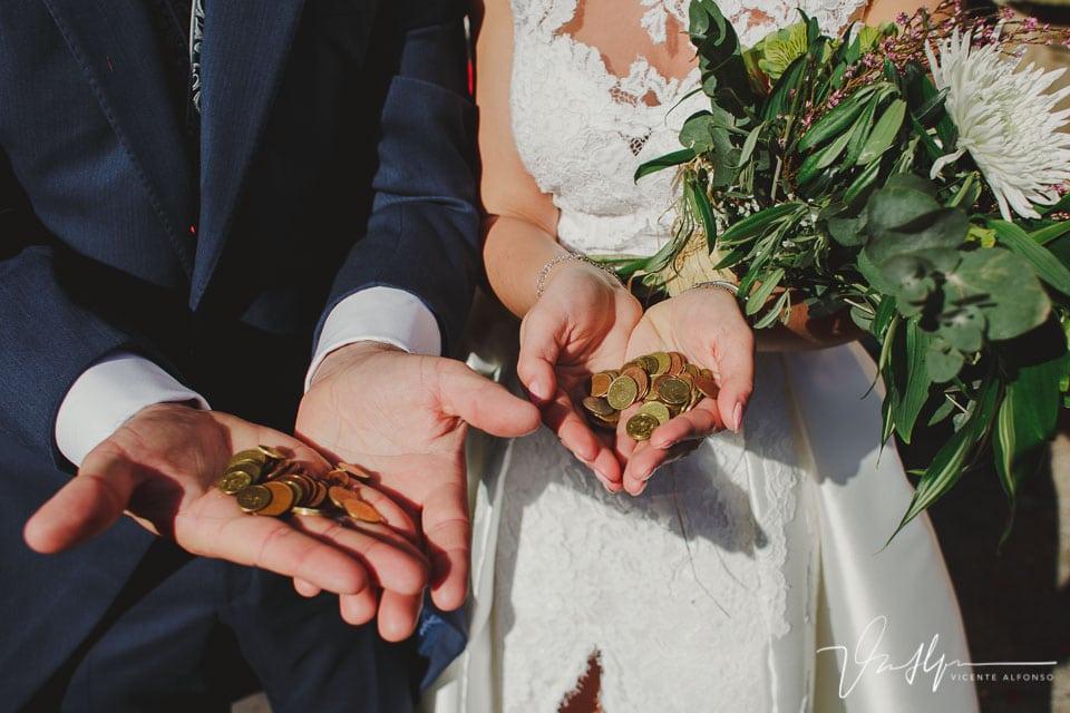 Detalle de monedas en las manos de los novios