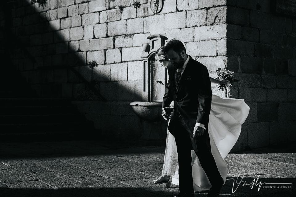 La novia estirando la cola de su vestido en un claro oscuro
