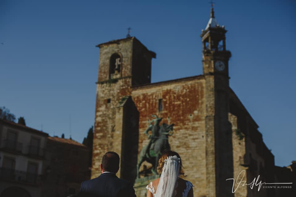 Novios de espalda con el caballo y la iglesia San Martín de Trujillo de fondo