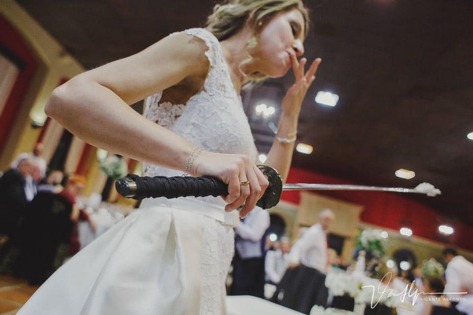 Novia chupándose el dedo después de cortar la tarta con una Katana