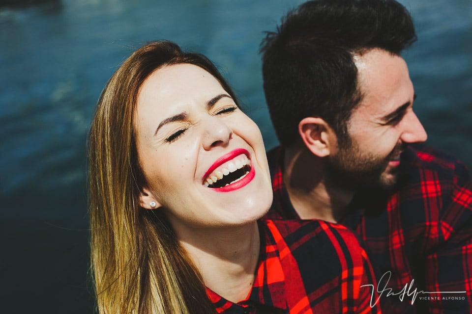 Mujer con la boca abierta riéndose a carcajadas