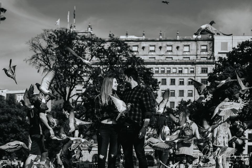Pareja mirándose en el centro de la plaça catalunya barcelona entre palomas
