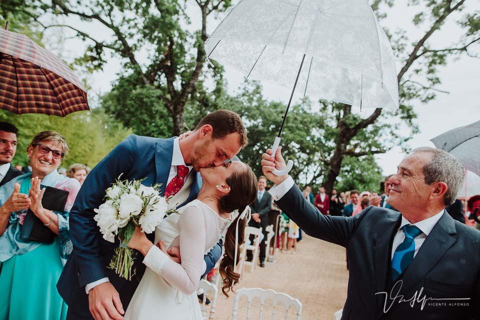 Novio besando a la novia bajo la lluvia después de casarse