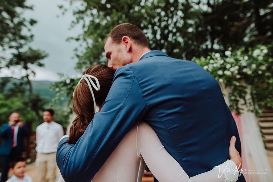 Novio besando y recibiendo a la novia en la ceremonia