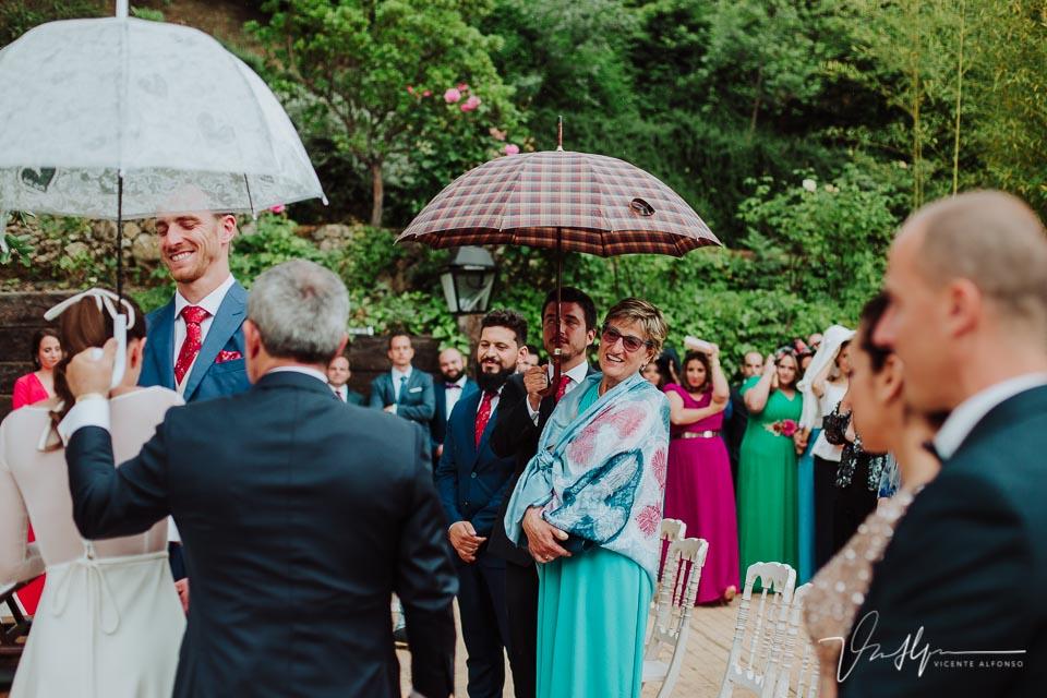 La madre del novio riendo bajo el paraguas
