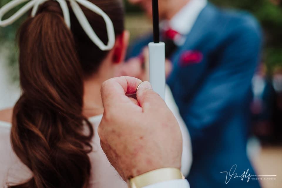 Padre sujetando el anillo de la novia y el paraguas