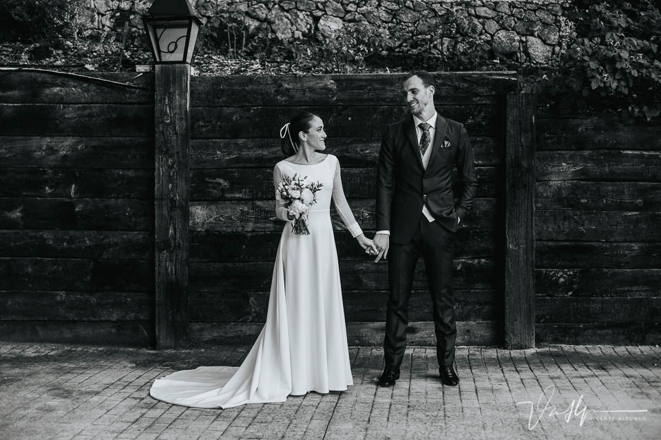 Fotografía de Novios en blanco y negro agarrados de la mano delante de un muro de madera