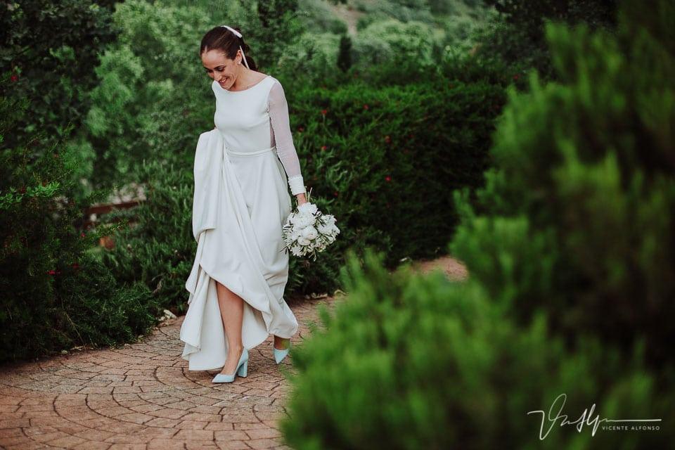 Novia andando con el vestido recogido