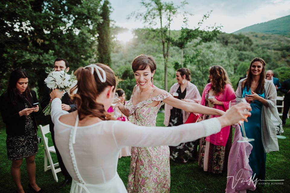Novia bailando al atardecer con una amiga italiana