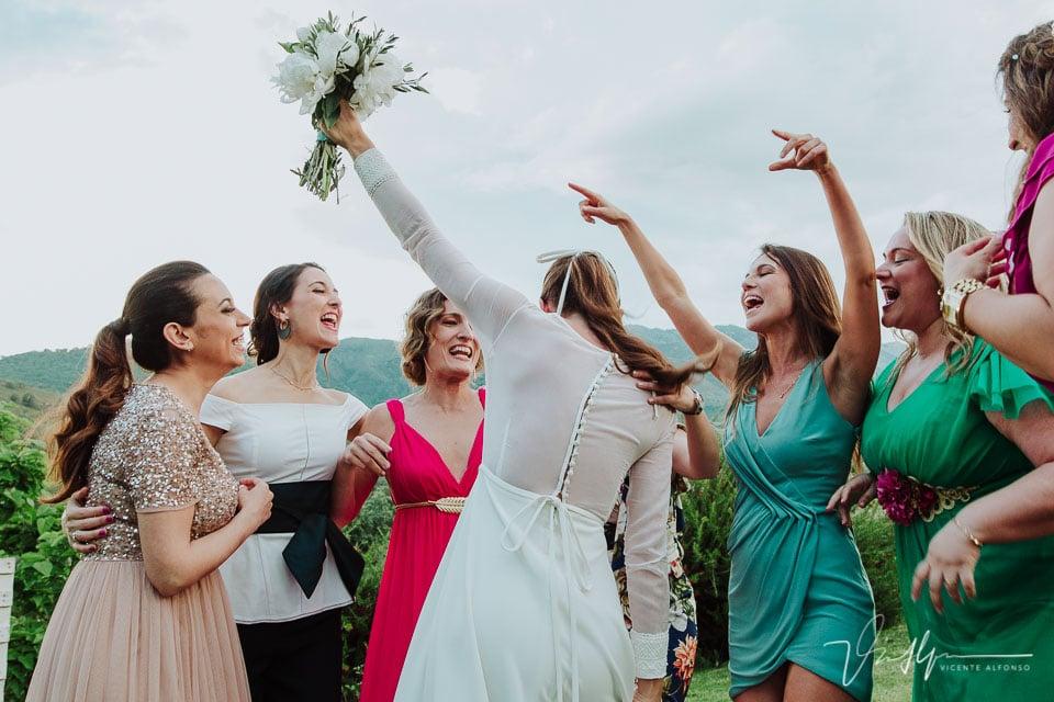 Novia levantando el ramo con sus mejores amigas
