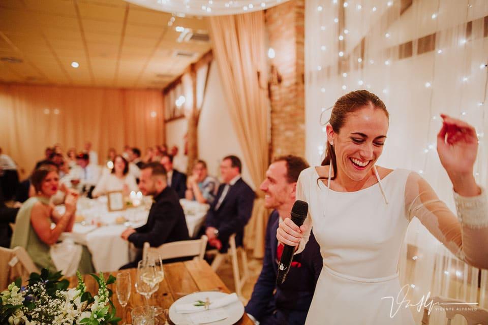 Novia riendo mientras dedica unas palabras en el banquete