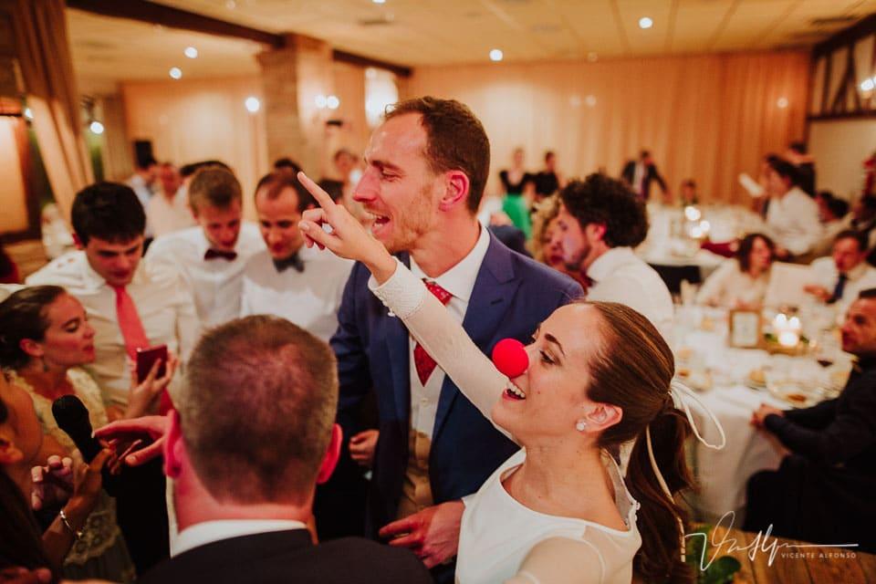 Novia con nariz de payaso celebrando en el banquete