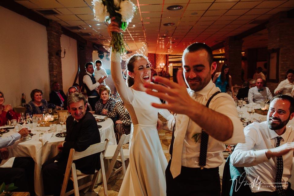 Novia bailando con amigo mientras entrega el ramo