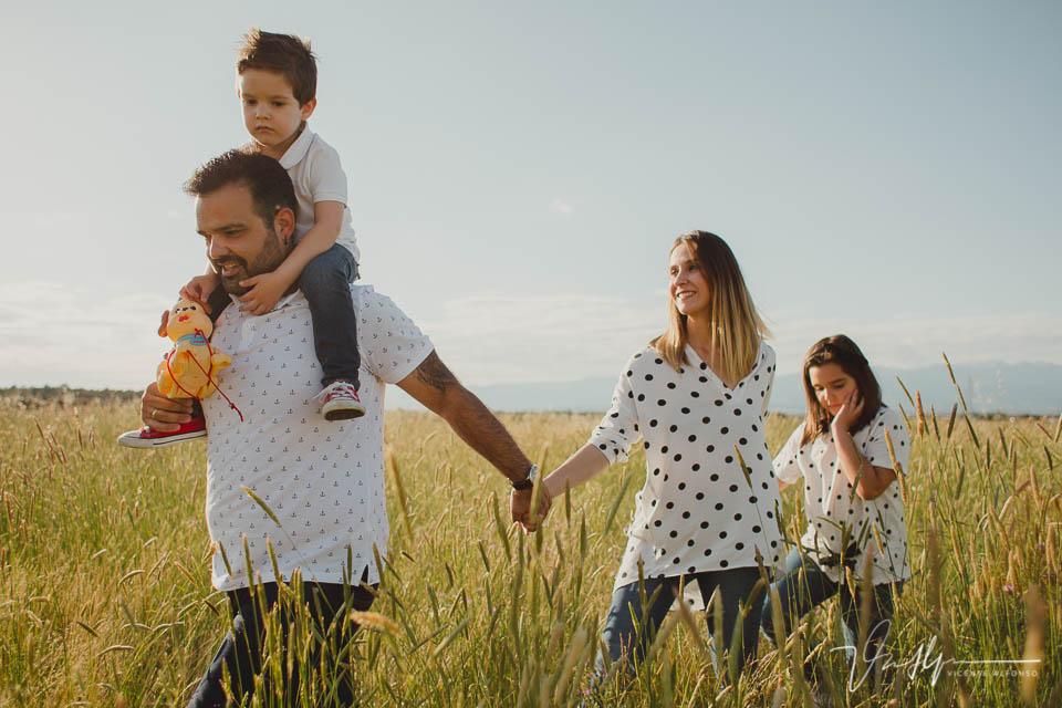 Toda la familia agarrada de la mano andando a través del campo