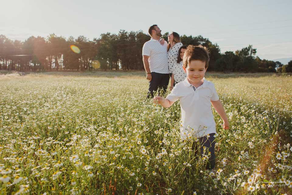 Niño pequeño andando delante de la familia en el campo