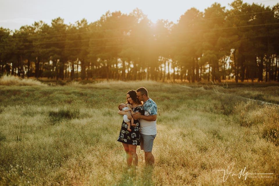 Familia abrazando bebé en el campo