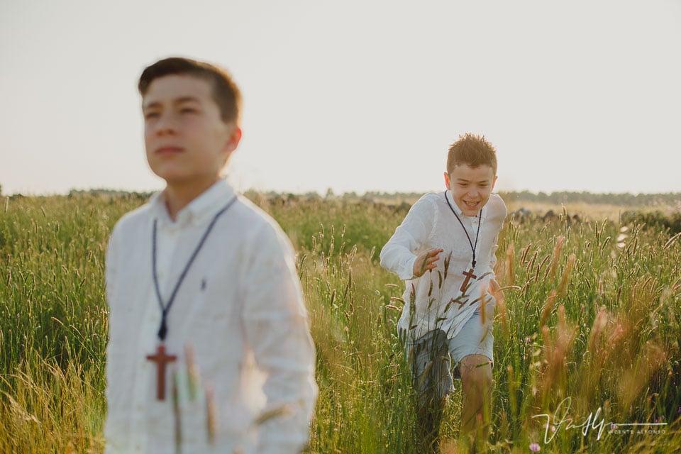niño corriendo en el campo con su hermano