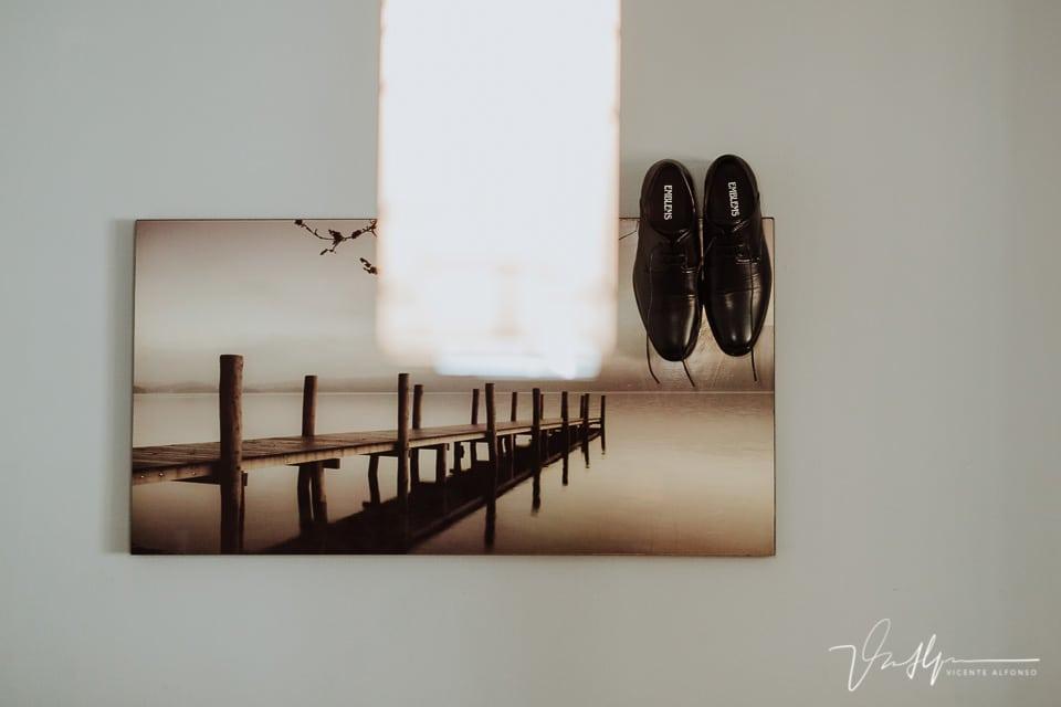 Detalle de los zapatos del novio colgados en un cuadro