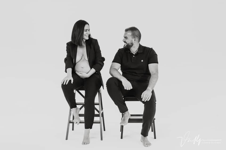 Pareja sentada en escaleras con embarazo