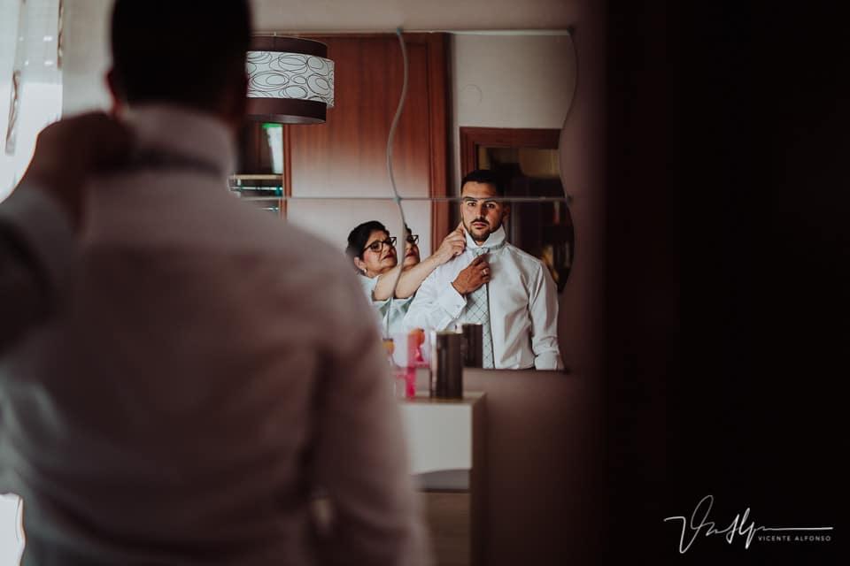 La madre del novio ayudando a vestirse