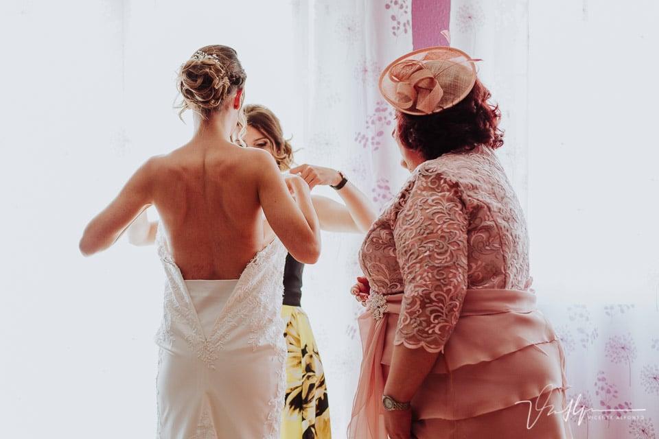 Amiga de la novia ajustando el vestido