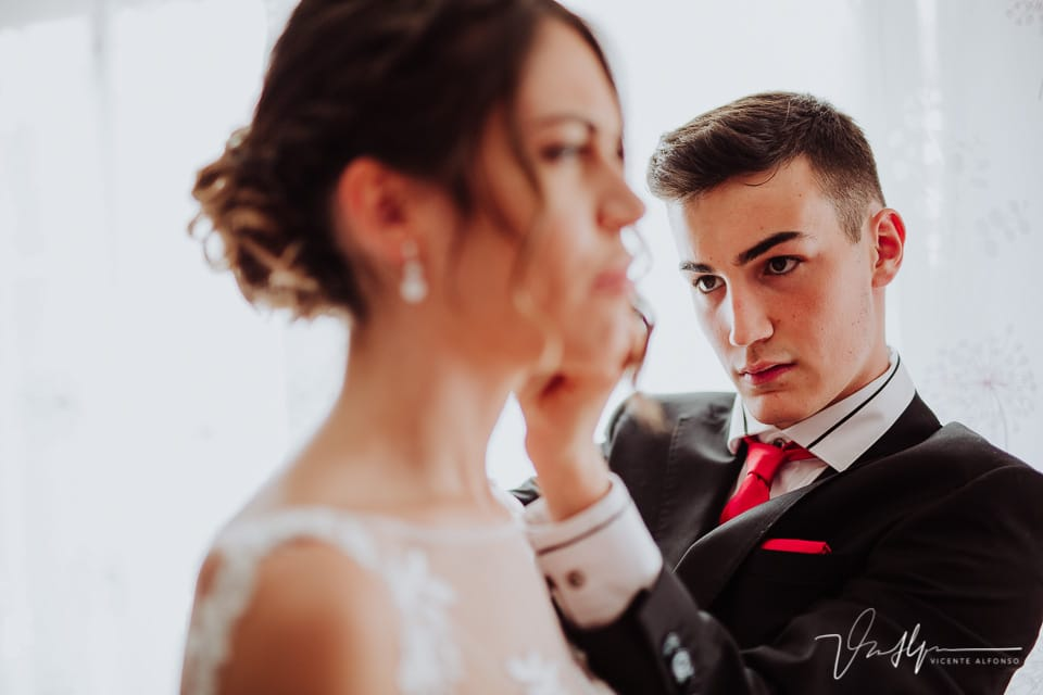 Hermano de la novia concentrado mientras la pone los pendientes