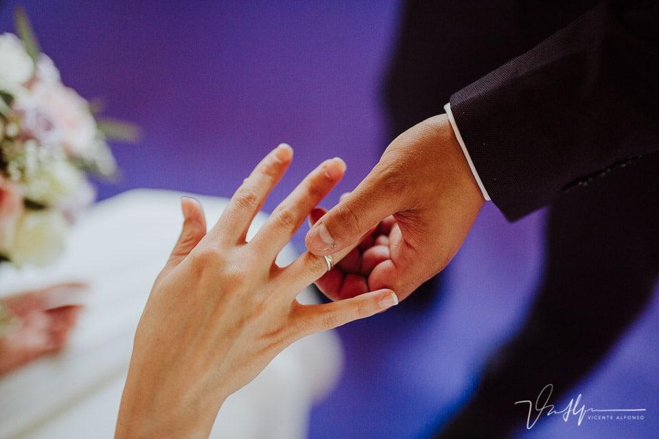 Novio poniendo anillo en la mano de la novia