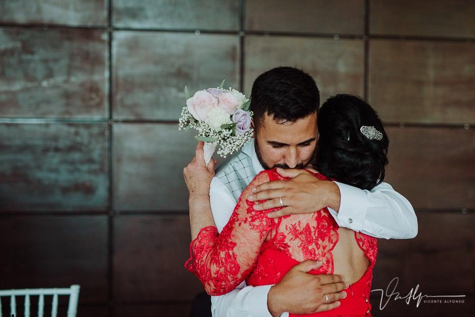 Abrazo del novio a su madre con un regalo