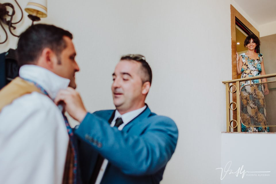 Amiga del novio mirando como le ponen la corbata