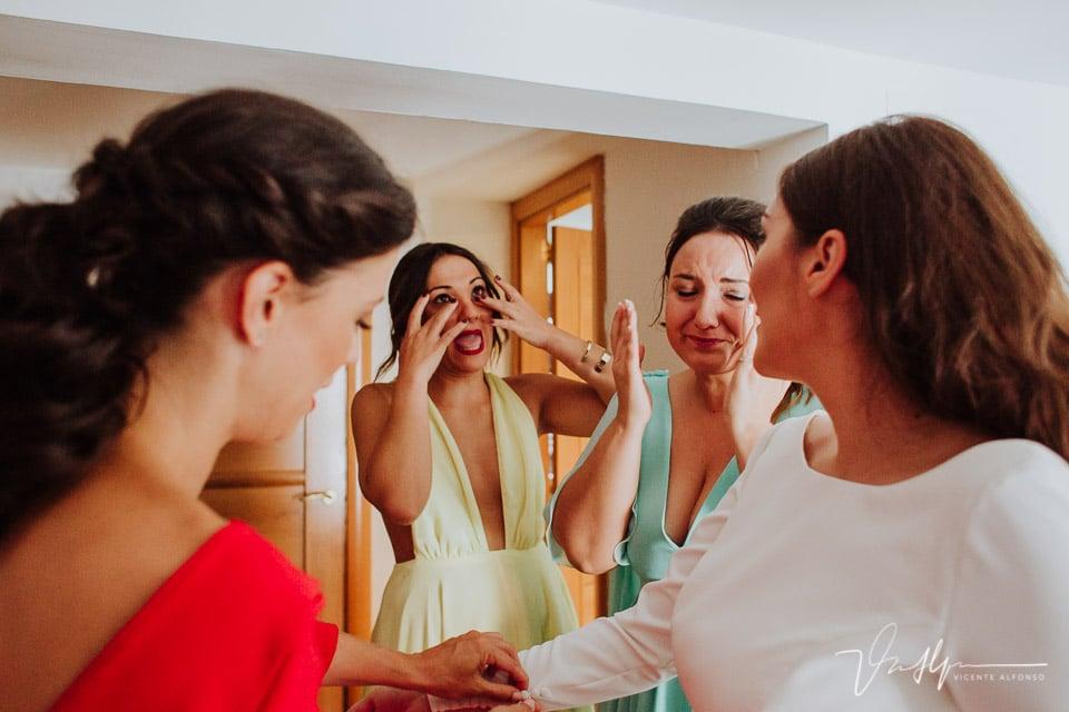 Amigas emocionadas mientras la novia se pone el traje