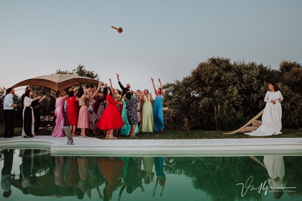 Novia lanzando el ramo con reflejo en una piscina