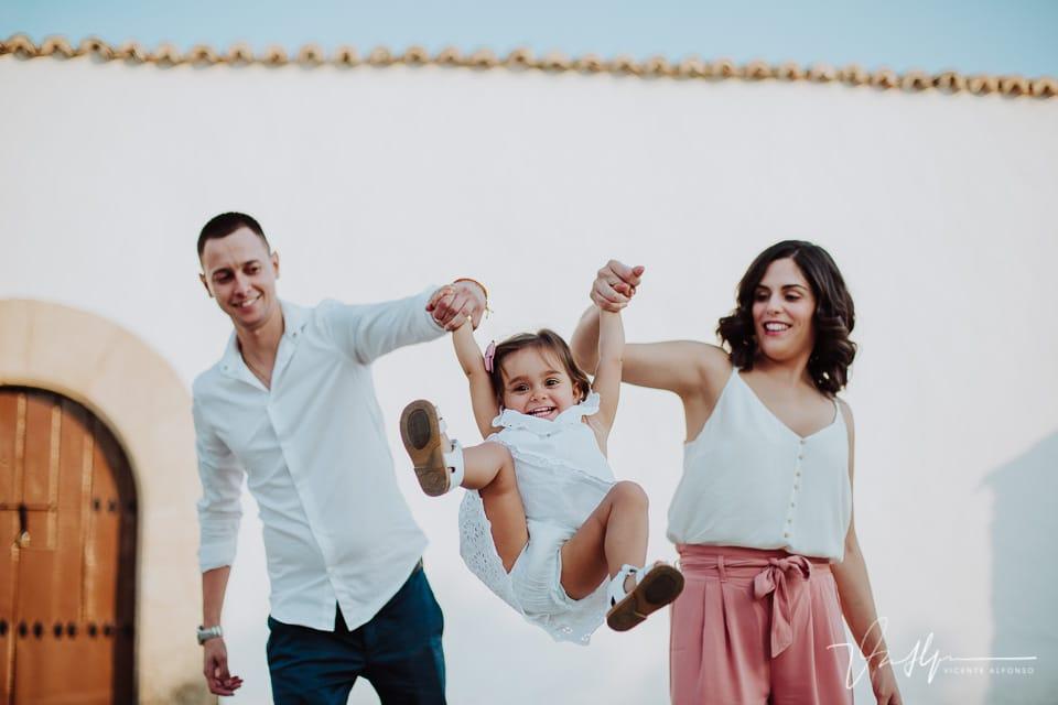 Padres haciendo volar a su hija